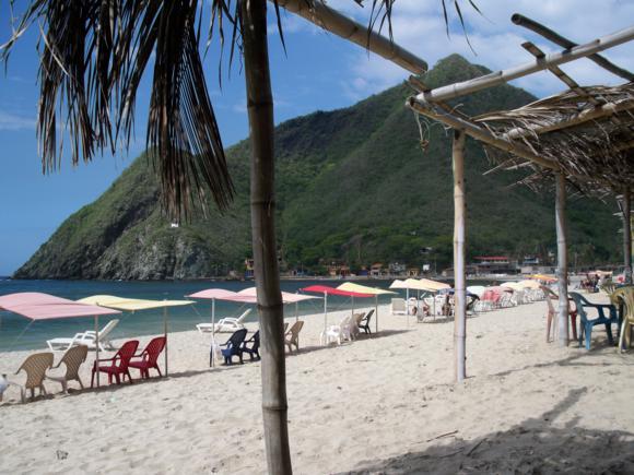 Montañas de verde intenso junto a la playa.