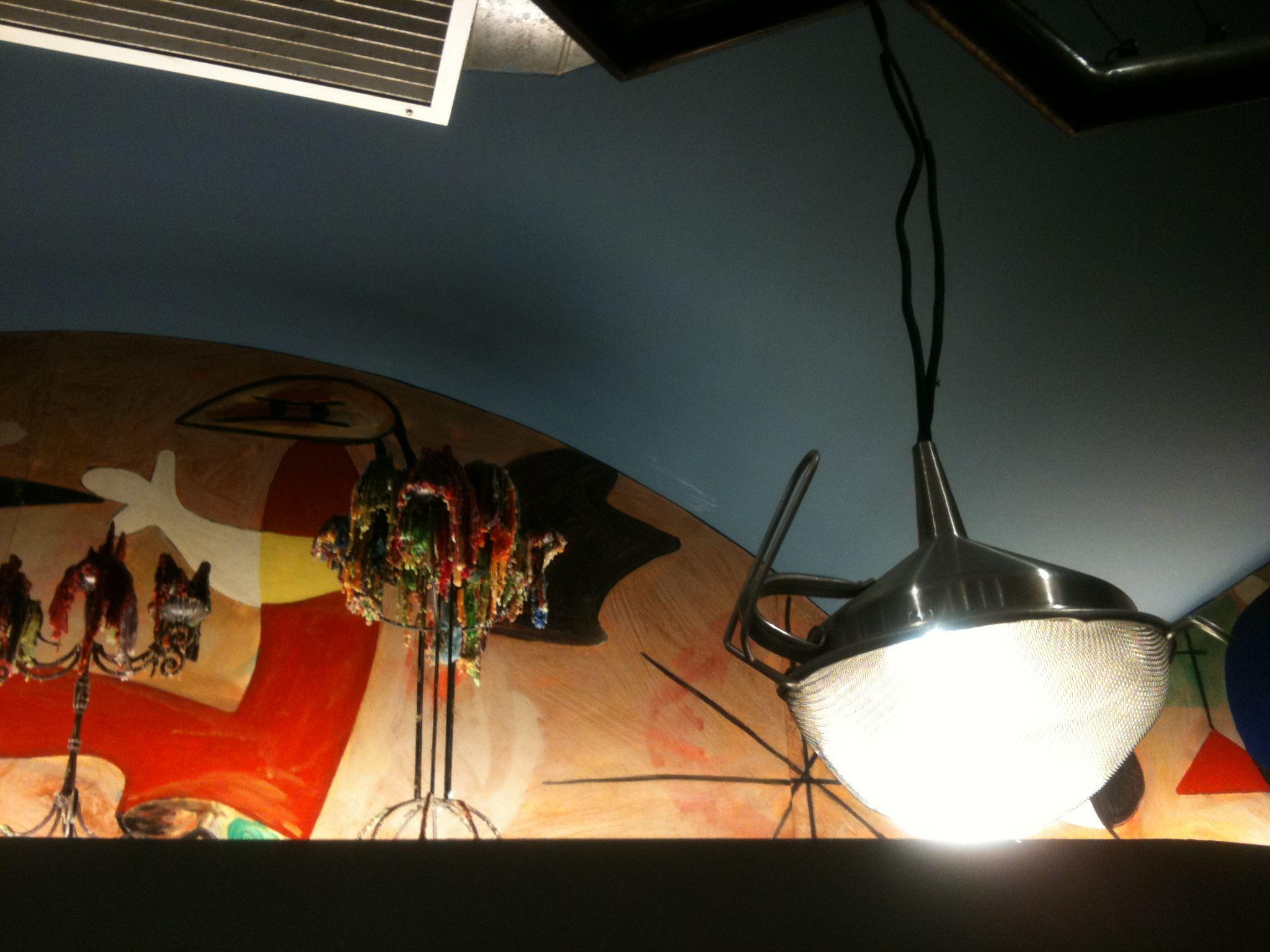 Un colador como lámpara y velas multicolores con pinturas mironianas...