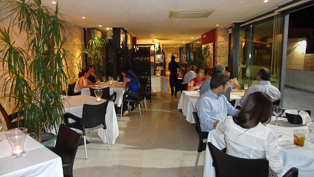El salón del restaurante con toda la cristalera con vistas a la ciudad.