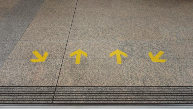 Flechas indicando dónde siturarse y dónde dejar pasar antes de subir al tren.