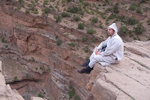 Rafa, con la chilaba de Moha en la piedra en voladizo sobre el río m'Goun.