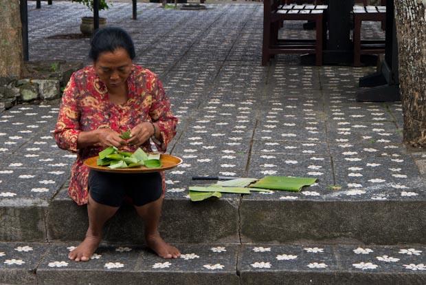 Señora, preparando cajitas de hoja de banano para las ofrendas.