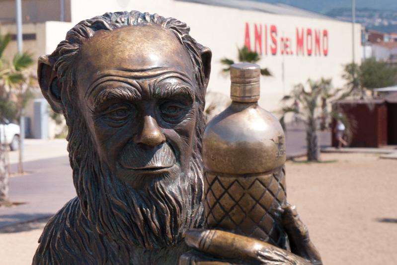 """El """"mono"""" con cara de Charles Darwin mirando la botella frente a la fábrica en Badalona."""